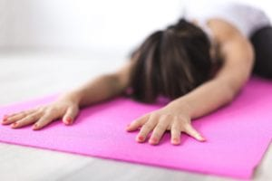 woman in a yoga pose on a pink mat
